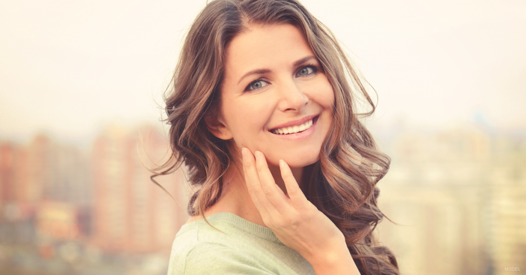 Smiling woman tilts head and gently touches face with hand