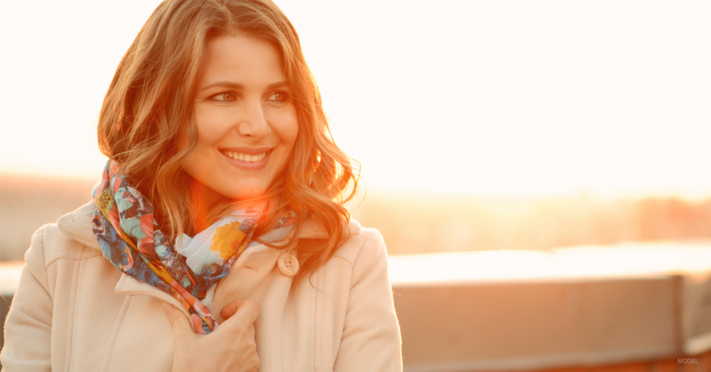 Woman with setting sun behind her looking right and smiling