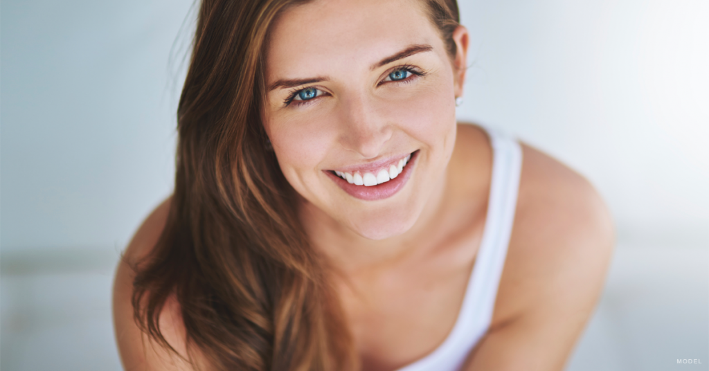 Woman in tank top looking up and smiling