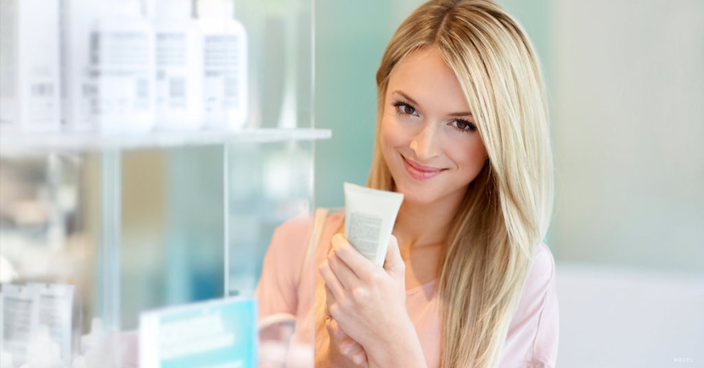 Beautiful woman looking at skincare products.