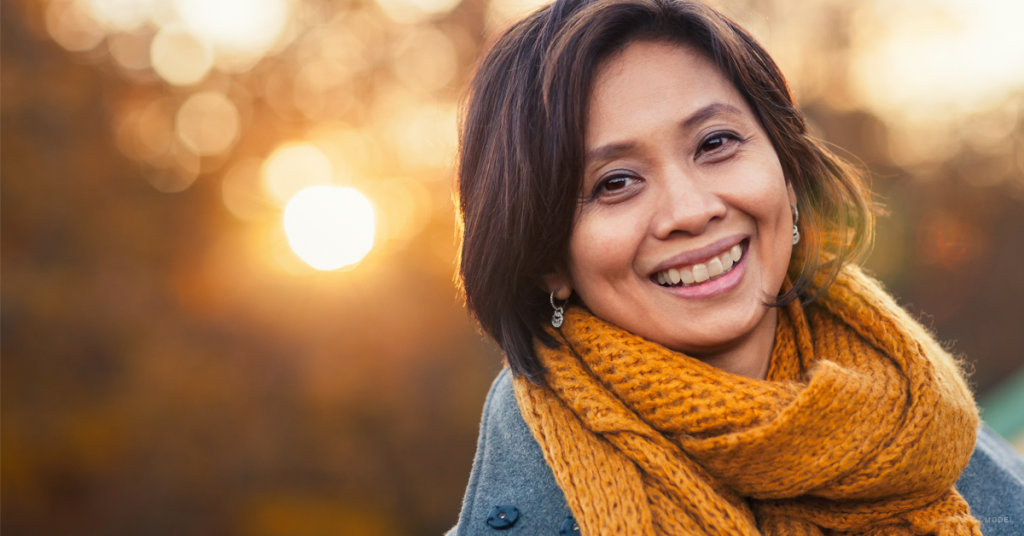 Brunette woman smiling after getting dermal fillers.