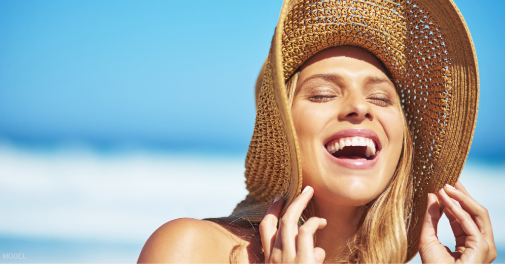 Head shot of woman laughing at beach with wide brimmed hat for sun protection