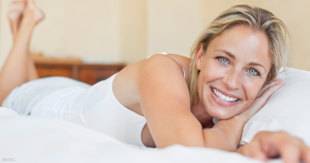 Woman smiling and lying on a bed on her stomach wearing tank top and shorts