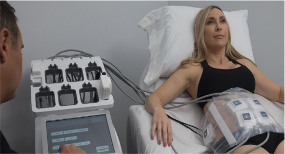 A woman demonstrating the setup of TruSculpt on her abdomen.