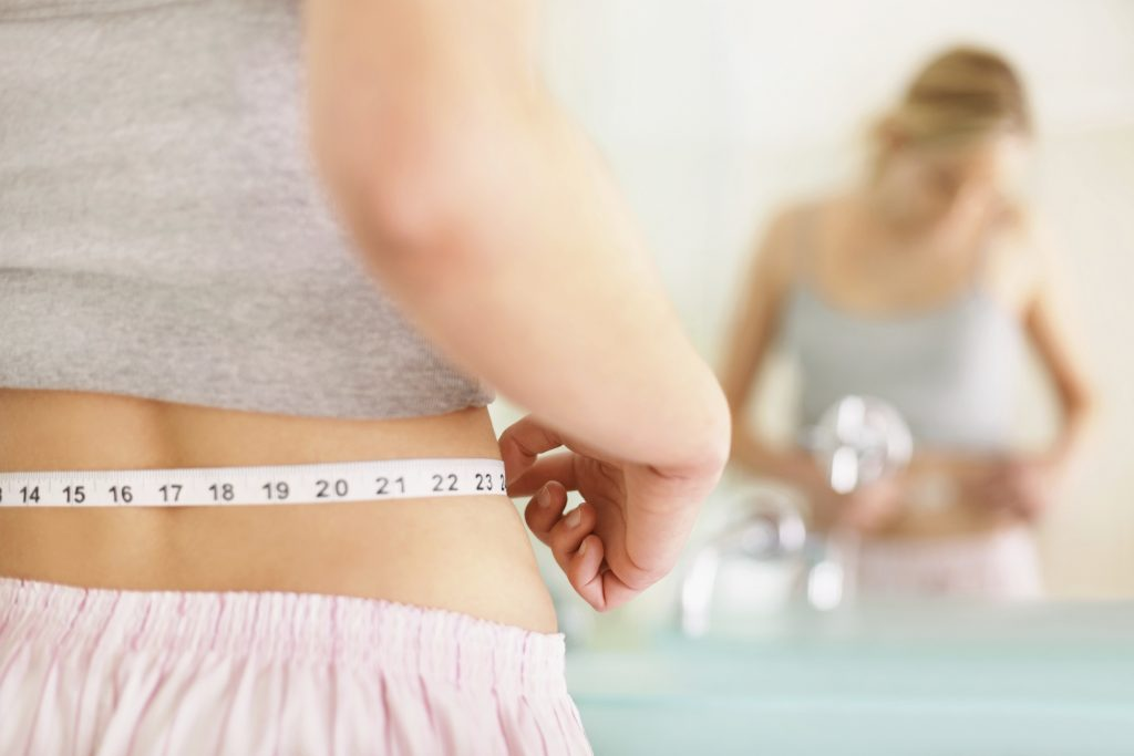 Woman measuring her waist reflected in mirror