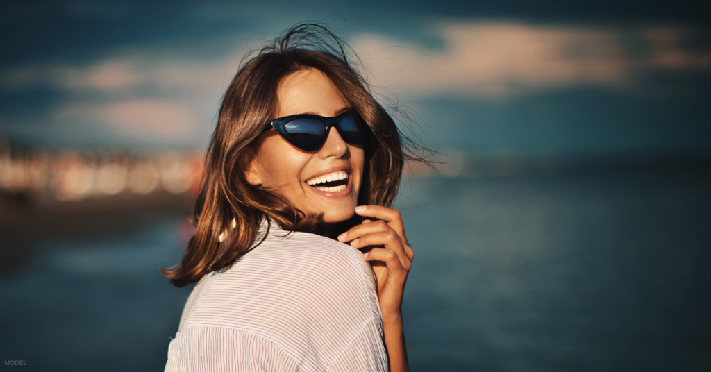 Woman in sunglasses looking back and smiling
